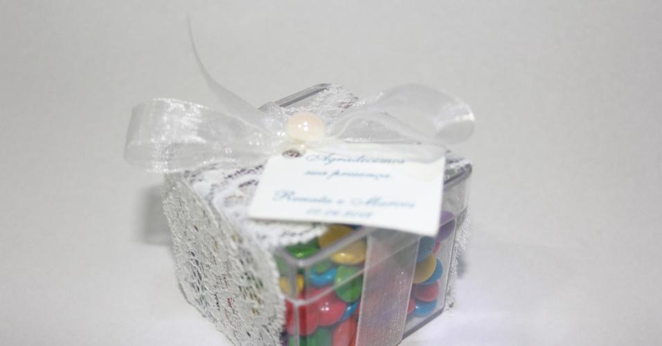Caixinha de acrílico com confeitos de chocolate; da E-lembranças (www.e-lembrancas.com.br), por R$ 5,50. Disponibilidade e preço pesquisados em junho de 2013 e sujeito a alterações
