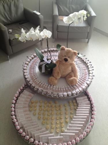 A mesinha de centro deste quarto de maternidade foi decorada com urso de pelúcia e acomodou as lembrancinhas de nascimento