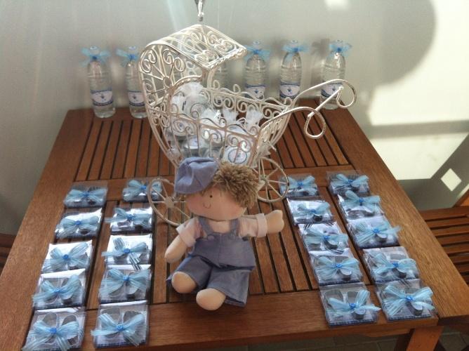 Boneco de pano, carrinho de ferro com lembrancinhas e água personalizadas decoram a mesa deste quarto de maternidade