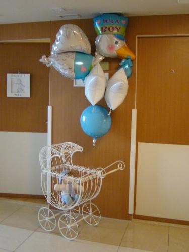 """Nesta foto o balão de gás hélio em forma de cegonha faz parte da decoração da porta do apartamento da maternidade, e traz os dizeres """"It's a boy"""" (é um menino, em inglês). O carrinho de ferro com um boneco de pano dentro faz alusão ao sexo do recém-nascido"""
