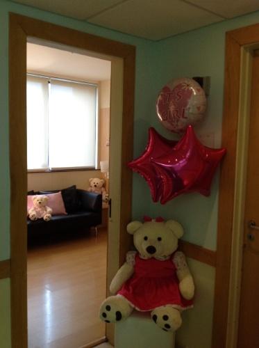 """Para enfeitar a entrada deste apartamento de maternidade a empresa de eventos Julubeca usou um urso de pelúcia e balões de gás hélio com os dizeres """"It's a girl"""" (é uma menina, em inglês)"""
