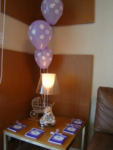 Ursinho de pelúcia, balões de gás hélio e lembrancinhas serviram para enfeitar a mesinha de canto deste quarto de maternidade decorado pela Julubeca