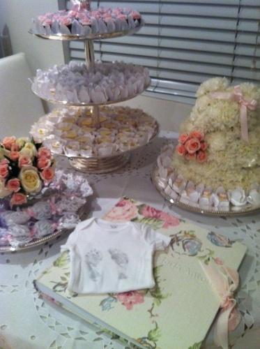 A mesa deste quarto de maternidade foi decorada com um urso feito de flores, doceira de prata, bandeja com pães de mel embrulhados na renda e livro de assinaturas para os visitantes