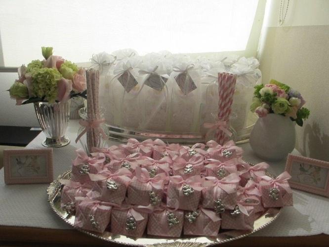 Esta mesa de quarto de maternidade foi decorada com uma bandeja de bem-nascidos embrulhados em rosa e com pingente de ursinho. Na parte de trás da mesa foram colocadas as lembrancinhas para os visitantes do bebê, que neste caso eram difusores de ambiente. O trabalho é da decoradora Deborah Doll (http://deborahdoll.blogspot.com.br)