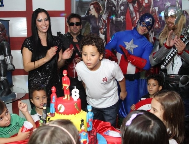 27.jun.2013 - Alex, filho do ex-jogador Ronaldo com Michele Umezu, apaga vela em seu aniversário de oito anos ao lado da mãe e de atores vestidos como super-heróis. A festa aconteceu em um buffet na Barra da Tijuca, no Rio de Janeiro