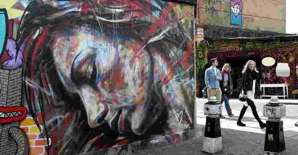 """Quando parlamentares britânicos aprovaram uma lei em 2003 para tornar ilegal o grafite em cidades inglesas, eles não esperavam que Londres se tornaria uma das capitais mundiais desse tipo de arte, com artistas locais ganhando fama internacional. David Walker, que pintou o mural """"Noivas em chamas"""" perto da conhecida rua Brick Lane, no leste de Londres, ganhou fama por suas apresentações de grafitagem """"ao vivo"""". Hoje ele vende em sua própria loja, versões impressas de seus trabalhos - BBC"""
