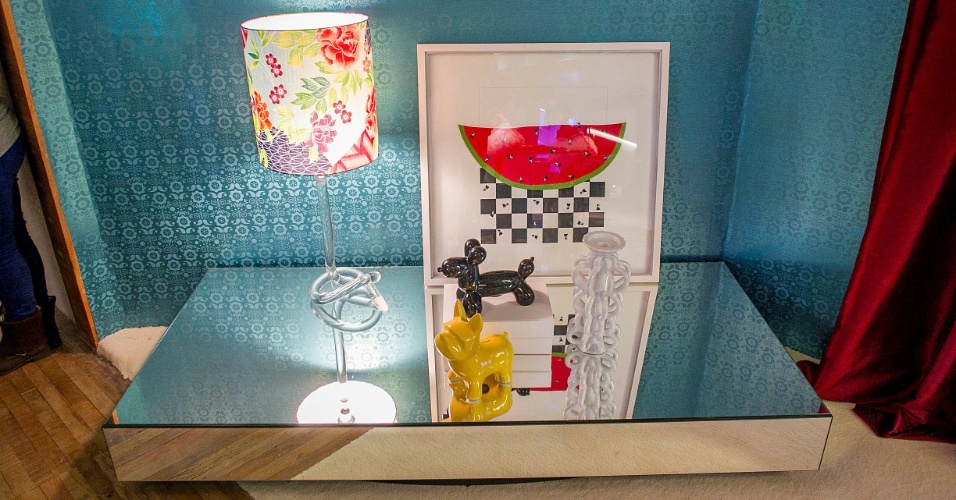 O excesso de cores e estampas é marcante na ?Suíte da Menina?. O papel de parede azul metalizado e texturizado serve de fundo para o móvel espelhado e a luminária com cúpula estampada de flores. (www.renatacoppola.com.br)