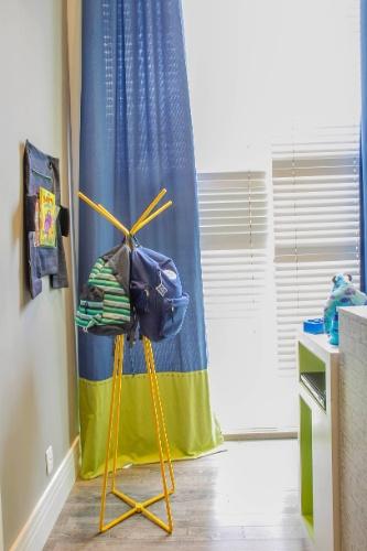 O mancebo amarelo organiza e deixa à mostra mochilas e sacolas do menino. Persianas e cortinas de tecido azul e verde filtram a luz que vem de fora e conferem aconchego ao canto de estudos da suíte. (www.cleliareginaangelo.com.br)