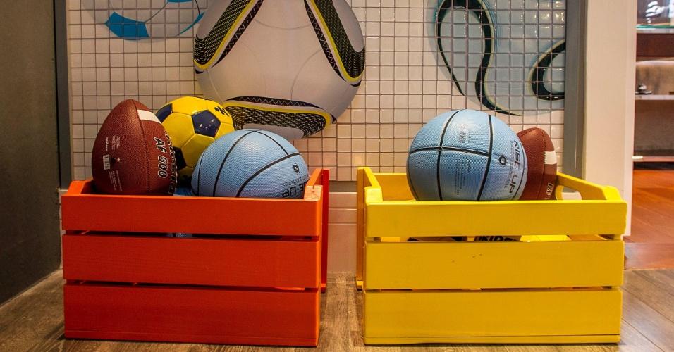 Pintados de amarelo e laranja, cores predominantes na decoração, os caixotes de madeira abrigam bolas para esporte de diferentes modalidades