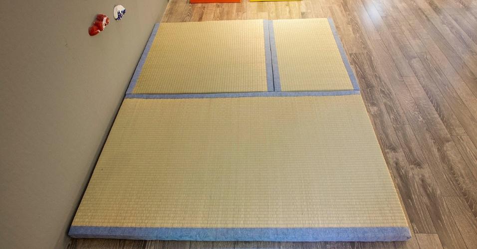 Próximo a parede de escalada, o tatame sobre o piso laminado serve para absorver impactos em caso de eventuais quedas. A parede faz parte da área de recreação da suíte do menino