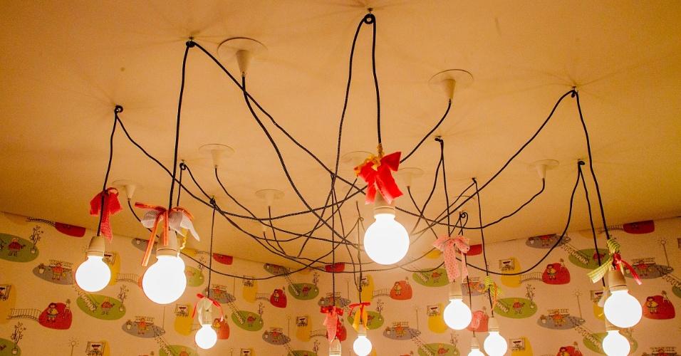 Um dos destaques do ambiente é a luminária pendente com lâmpadas de bulbos, suspensas por fios entrelaçados. (www.camilarosa.arq.br)