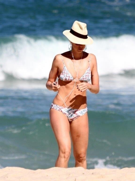 5.jul.2013 - De chapéu, Luana Piovani caminha na praia do Leblon, na zona sul do Rio