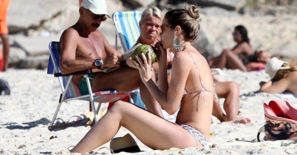 5.jul.2013 - Luana Piovani toma água de coco na praia do Leblon, na zona sul do Rio