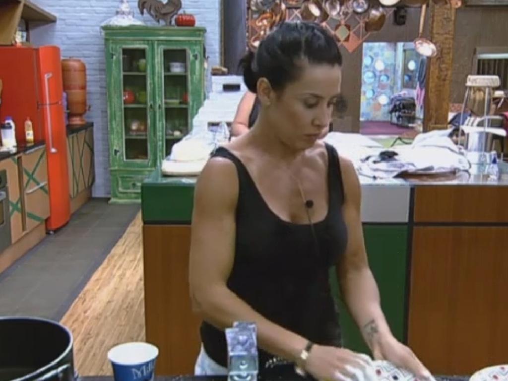 5.jul.2013 - Sem água encanada, o jeito é improvisar. Scheila Carvalho usa caneca e balde para lavar a louça.