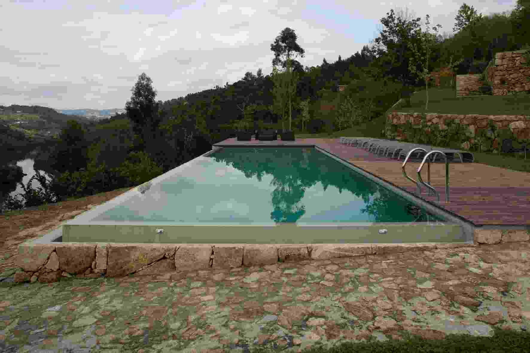 Tirando proveito do relevo acidentado, a piscina de borda infinita e o deck foram projetados de forma a permitir a seus usuários uma vista panorâmica para o rio Tâmega e os verdes campos. A RF House foi projetada por Nuno Graça Moura em Marco de Canaveses, no norte de Portugal - Leonardo Finotti/ UOL