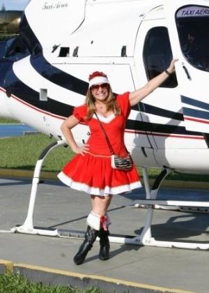 20.dez.2009 - Vestida de Mamãe Noel, a atriz Susana Vieira embarca em helicóptero para distribuir presentes de Natal em comunidade carente do Rio de Janeiro