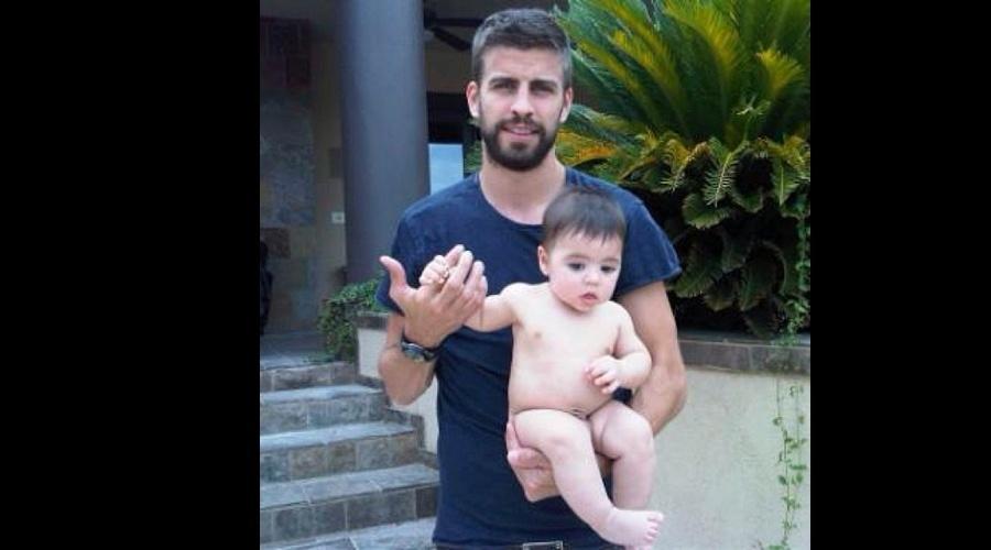 14.jul.2013 - Shakira divulgou uma imagem do marido, o jogador de futebol Gerad Piqué, com o filho do casal, Milan, no colo. Na foto, o menino aparece pelado