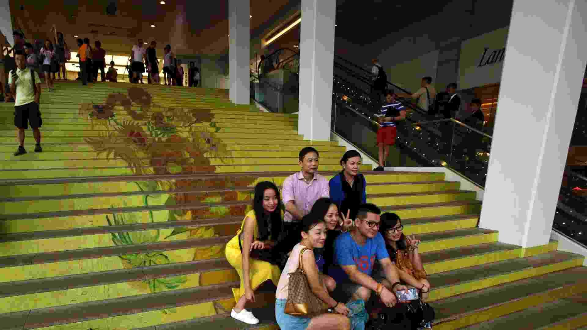 """15.jul.2013 - Grupo posa em escadaria com reprodução de """"Os Girassóis"""", de Van Gogh, em Hong Kong.  Criada em conjunto com o Museu Van Gogh, em Amsterdã, a coleção tem reproduções de quadros do artista com alta qualidade e da forma mais fiel possível. A mostra tem, além de """"Os Girassóis"""", obras como """"Amendoeira em Flor"""" e """"Boulevard de Clichy"""". Montada em um shopping na zona portuária, a exposição vai até o dia 4 de agosto - Bobby Yip/Reuters"""