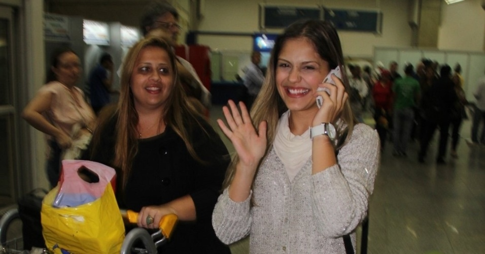 15.jul.2013 - Jéssika Alves acena para fotógrafos ao desembarcar no aeroporto internacional do Rio de Janeiro