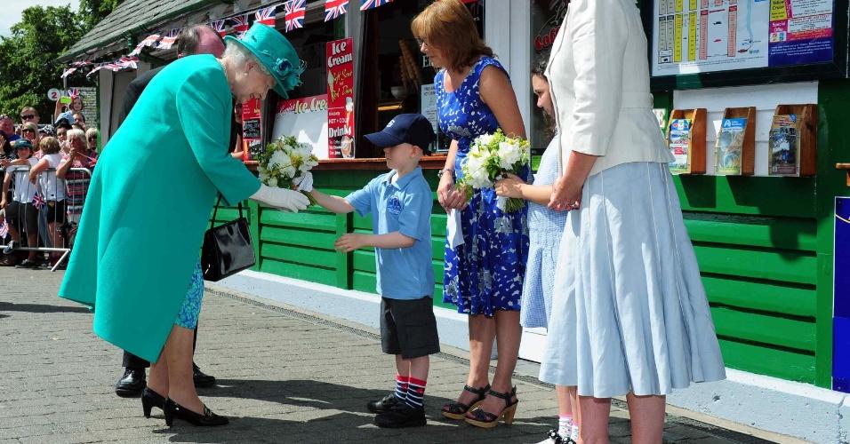 17.jul.2013 - Rainha Elizabeth 2ª recebe flores de Daniel Dixon, de seis anos, no píer Bowness-on-Windermere, em Cumbria, Inglaterra