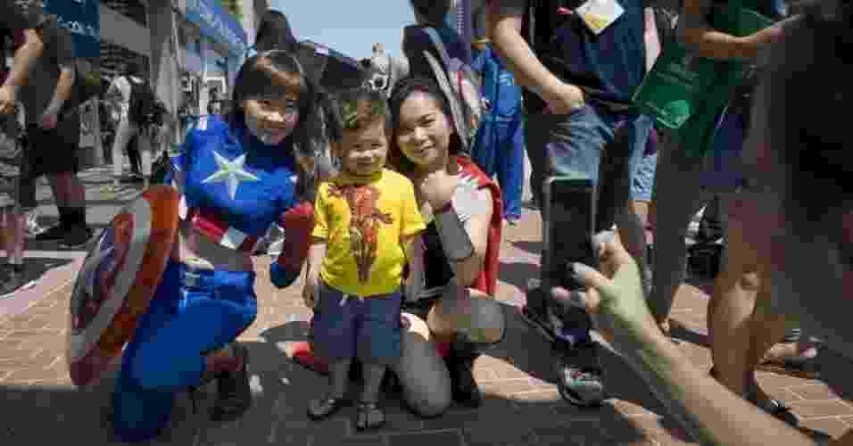 18.jul.2013 - Mulheres vestidas como Capitão América e Thor, com o garotinho improvisando um cosplay de Homem de Ferro no meio - David Maung/EFE