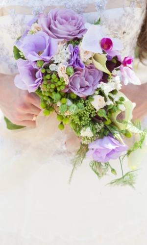 Buquê de rosas, orquídeas, folhagens e sementes. A mistura de elementos cria um resultado exótico e vistoso