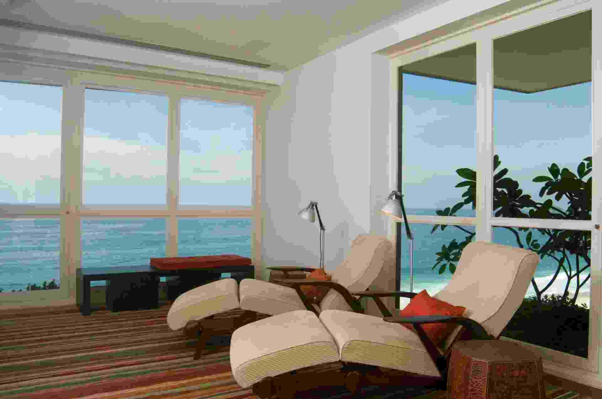 No segundo andar do apartamento dúplex, de 600 m², em São Conrado (RJ), a arquiteta Izabela Lessa transformou a sala íntima, anexa à suíte do casal, em um espaço de leitura e relaxamento, com poltronas (Etel) do tipo espreguiçadeira. Com uma fachada de vidro, o ambiente se integra à paisagem praiana - MCA Estúdio/ Divulgação