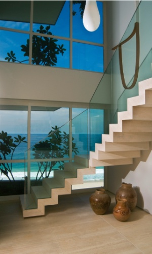 Para transformar os dois apartamentos em um dúplex, projeto de autoria da arquiteta Izabela Lessa, foi preciso quebrar uma laje para implantar a escada que fica de frente à fachada de vidro. Por estar presa à parede por fixadores imperceptíveis, fica uma sensação de que a estrutura flutua