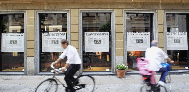 Ciclistas passam em frente a loja da Dolce & Gabbana em Milão. A grife italiana fechará por três todas as suas lojas em protesto contra a condenação por evasão fiscal - Alessandro Garofalo/Reuters