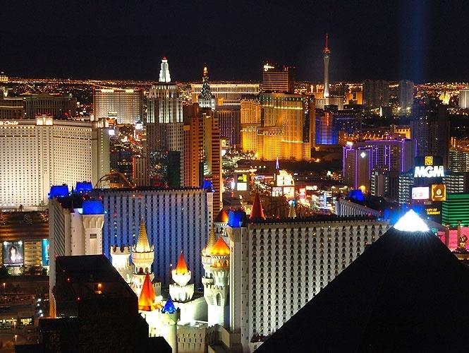 Vista noturna do Las Vegas, com as torres do Excalibur coloridas e iluminadas