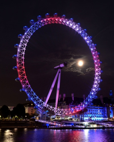 22.jul.2013 - A roda-gigante London Eye é iluminada de azul e vermelho para comemorar o nascimento do príncipe de Cambridge, filho da duquesa de Cambridge e do príncipe William