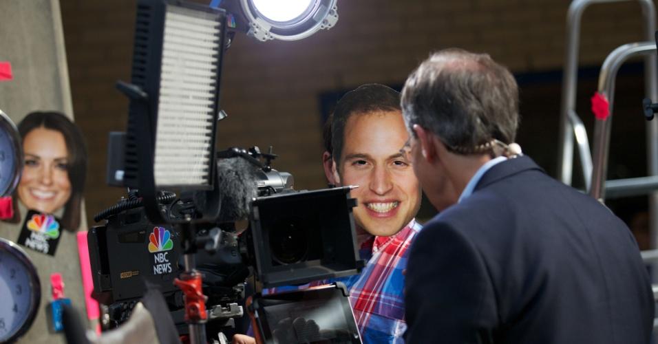 22.jul.2013 - Cinegrafista de uma rede de TV usa máscara do Príncipe William em área reservada à imprensa em frente à ala Lindo do Hospital St. Mary