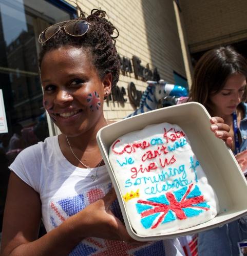 """22.jul.2013 - Fã da família real posa com um bolo em homenagem ao bebê real. """"Vamos Kate, não aguentamos mais esperar. Nos dê algo para celebrar"""", diz a mensagem no bolo"""