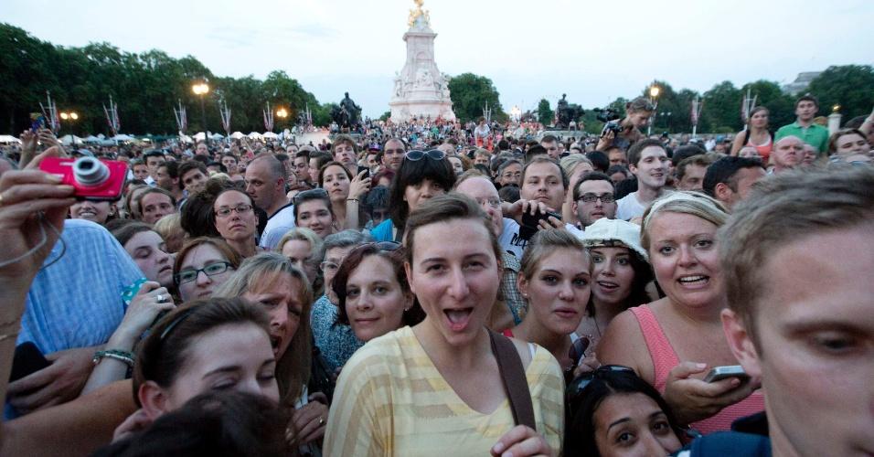 22.jul.2013 - Uma multidão de pessoas tenta se aproximar do portão do Palácio de Buckingham onde um documento assinado pelo médico anuncia o nascimento do príncipe de Cambridge