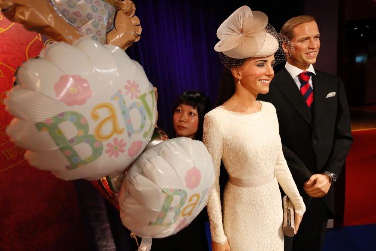 23.jul.2013 - Funcionária do museu Madame Tussauds de Tóquio arruma balões que celebram o nascimento do bebê real, ao lado das figuras de Kate e William