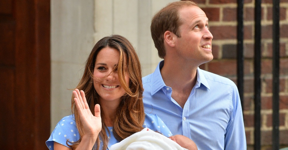 23.jul.2013 - Kate acena para os súditos ao sair do hospital com o bebê real com o marido, príncipe William