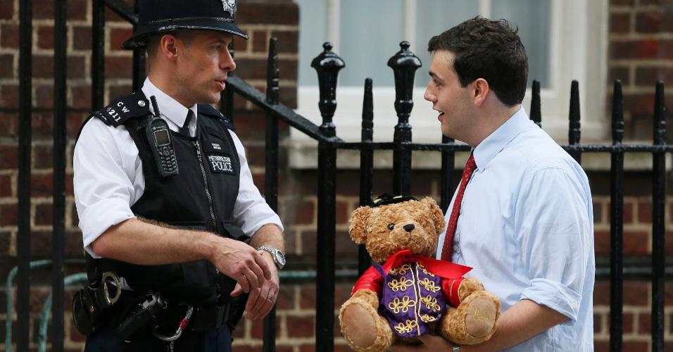 Homem carrega urso de pelúcia de presente para o bebê real, em frente ao hospital St.Mary