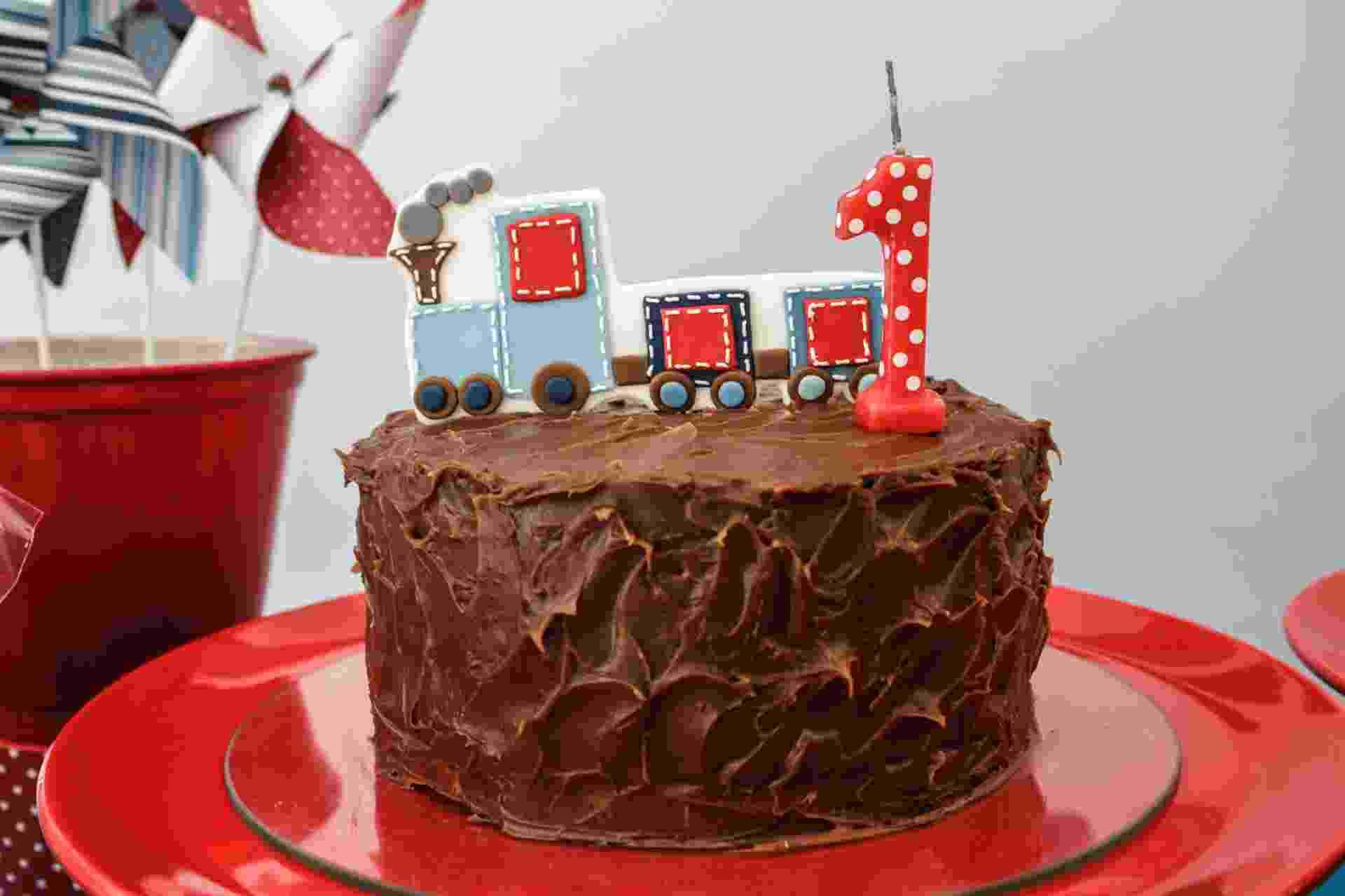 O suculento bolo coberto com uma camada generosa de chocolate é uma receita de Nika Linden (www.nikalinden.com.br). O trenzinho que enfeita o topo combina com a decoração da festa Brincadeiras de Menino, organizada pela (www.caraminholando.com.br) - Divulgação