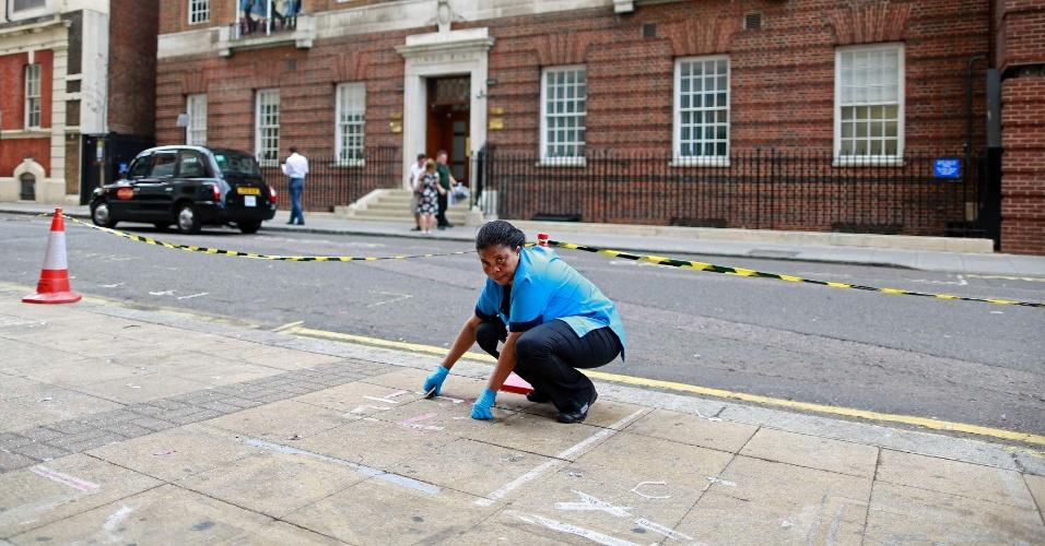 24.jul.2013 - Faxineira limpa calçada em frente à ala Lindo do hospital St. Mary