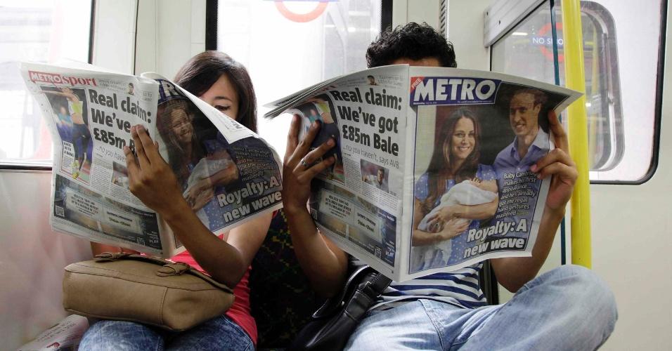 24.jul.2013 - Passageiros do metrô de Londres lêem jornais com manchete sobre a apresentação do filho de Kate e William ao público. A imprensa do Reino Unido destacou o momento em que os Duques de Cambridge deixaram o hospital St. Mary com o bebê real, que nasceu no dia 22 de junho