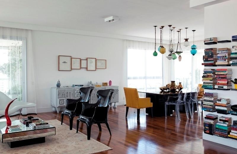 A sofisticação da sala de estar, interligada às salas de jantar e de televisão, fica por conta da mesa de centro revestida com espelho, do tapete Ziegler paquistanês e das poltronas pretas de policarbonato. As cadeiras incolores e as poltronas em tecido amarelo da sala de jantar iluminam e trazem leveza ao ambiente decorado por Leonardo Di Caprio