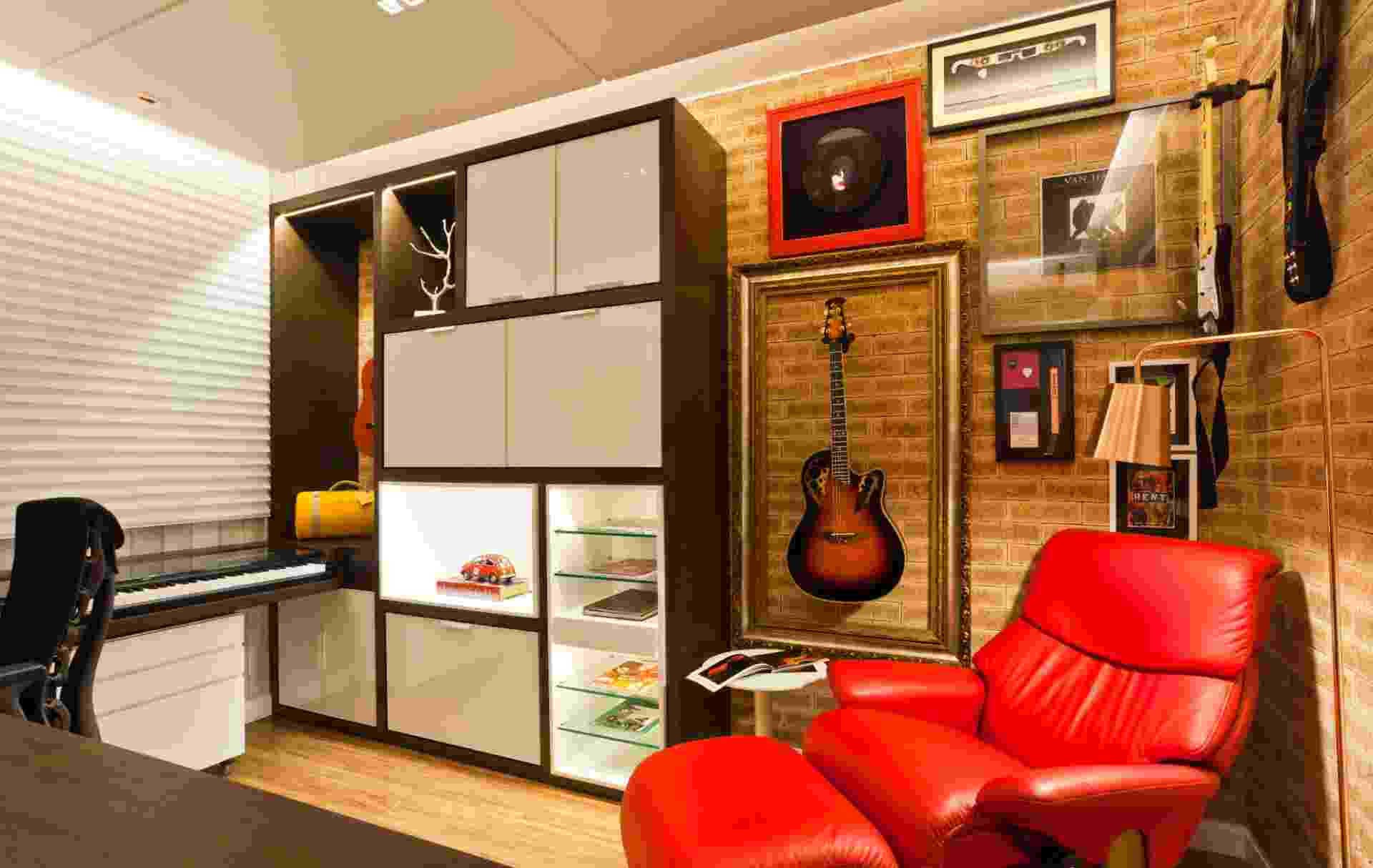 Com 11 m², o estúdio faz parte do apartamento de um fã de rock; acomoda mesa, duas guitarras e teclado em móvel retrátil, com gaveta deslizante e tampo de vidro. No projeto de Juliana Pippi, o ambiente multifuncional proporciona ao proprietário toda a infraestrutura para estudar, trabalhar e ensaiar - Divulgação