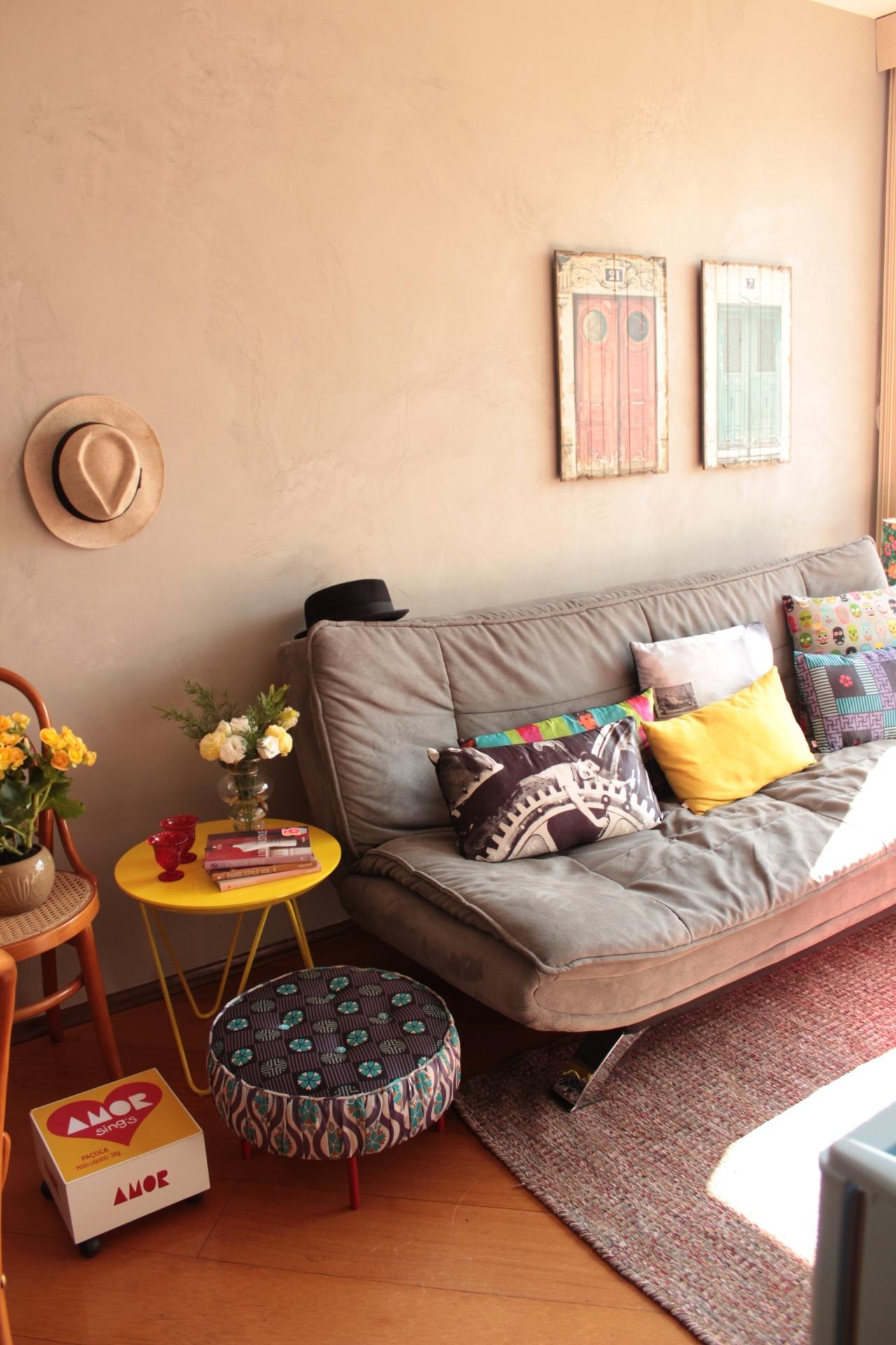 No projeto da designer de interiores Ingrid Hirsch, a sala do apartamento de 40 m² ganhou ares mais rústicos graças à pintura especial. As paredes foram cobertas com tinta que imita cimento queimado. O mix de estampas das almofadas, o chapéu pendurado na parede e o conjunto de móveis e objetos ao lado do sofá-cama conferem ainda mais charme e personalidade à decoração