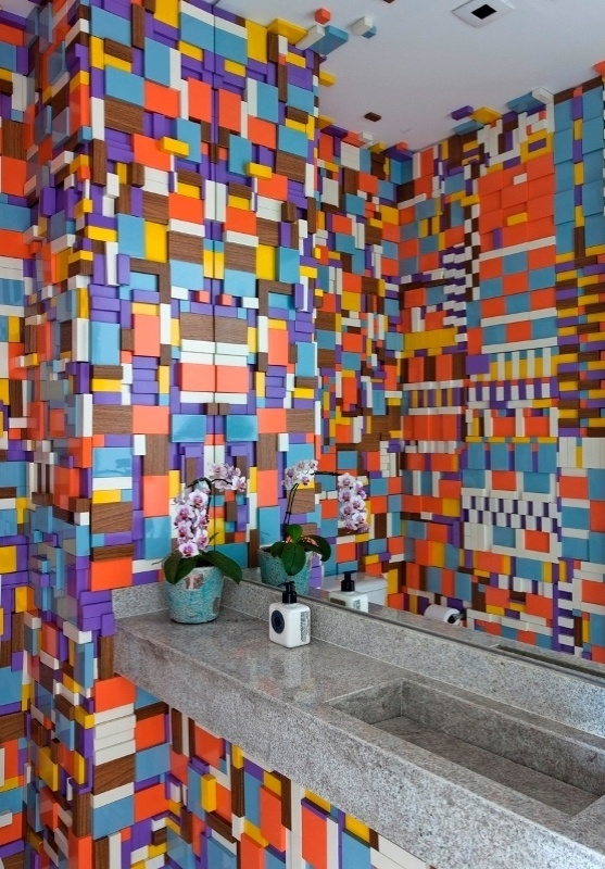 O lavabo projetado pelo decorador Leonardo Di Caprio é revestido com bloquinhos de MDF cortados em tamanhos múltiplos, laqueados em cores escolhidas pela moradora. Posicionadas aleatoriamente, as peças criam a impressão de um colorido pixelado em 3D