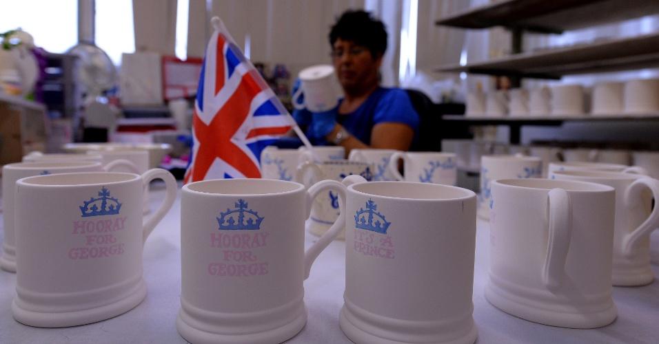 25.jul.2013 - Trabalhadora decora caneca comemorativa pelo nascimento do príncipe de Cambridge, George Alexander Louis, em uma loja de cerâmica em Stoke-on-Trent, Staffordshire, Inglaterra