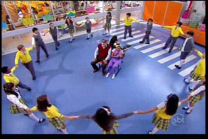 26.jul.2013 - Crianças formam um carrossel em volta de Firmino e diretora Olívia