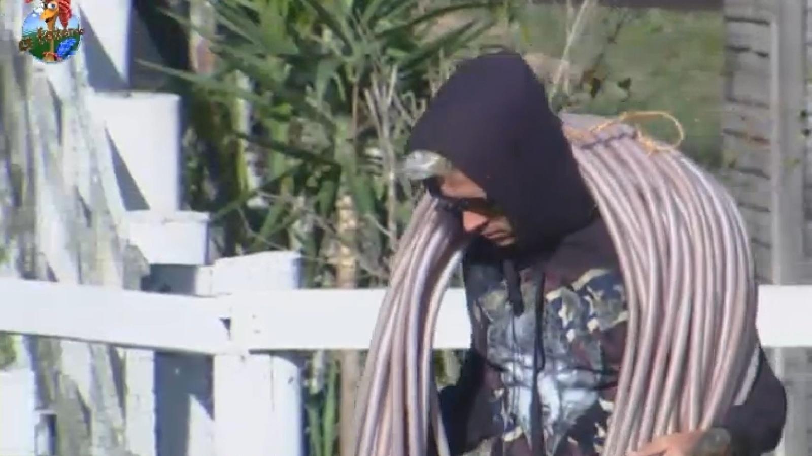 28.jul.2013 - Mateus Verdelho carrega a mangueira enquanto cumpre tarefas na manhã deste domingo
