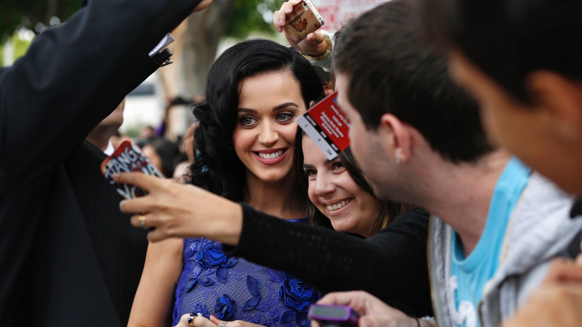 28.jul.2013 - Dubladora da personagem Smurfette, a cantora Katy Perry posa com fãs em Los Angeles, na pré-estreia do filme