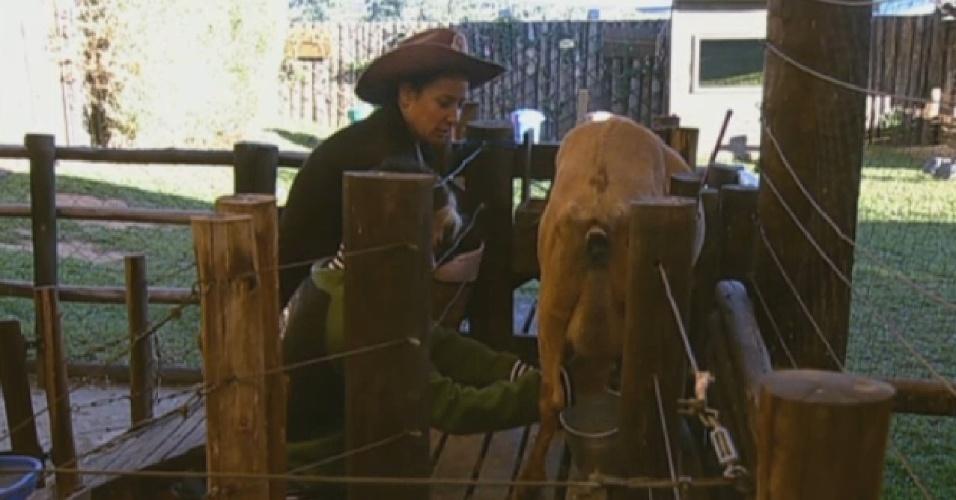 29.jul.2013 - Yudi Tamashiro cuida das cabras com auxílio de Scheila Carvalho