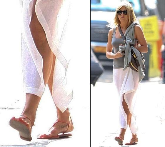 """A atriz Jennifer Aniston exibe a tatuagem que fez no seu pé direito. Ela escreveu """"Norman"""", nome de seu cachorro da raça corgi-terrier, morto em maio de 2011, com 15 anos de idade"""